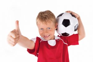 Junge mit Fußball lachend